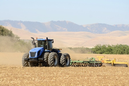 harrow: A tractor pulls a disc harrow system implement to smooth over a dirt field in preperation for planting in central California