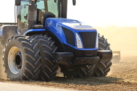 A tractor pulls a disc harrow system implement to smooth over a dirt field in preperation for planting in central California