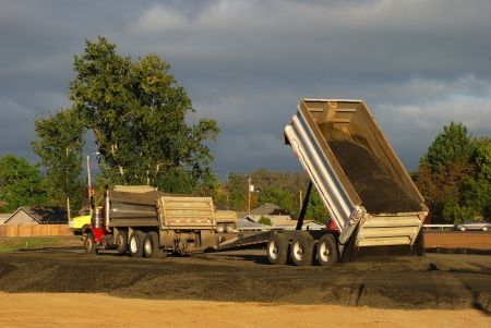 Dump truck and trailer laying down gravel base while working on a new tennis center, Stewart Park, Roseburg OR photo
