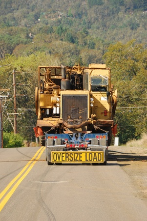 Lowboy moving a large box scaper from a construction site in Roseburg Oregon