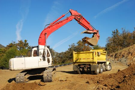 back hoe: Large track hoe exchavator filling a dump truck at a new commercial construction site in Roseburg Oregon Stock Photo