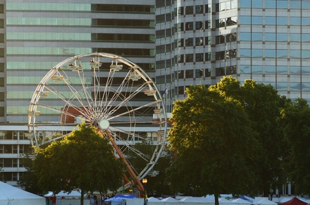amusment: A colorful ferris wheel lights up against the city skyline of Portland Oregon during the Rose Festival CityFair