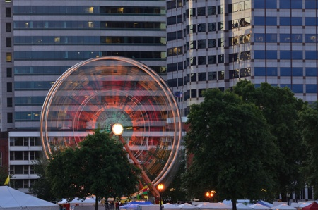 A colorful ferris wheel lights up against the city skyline of Portland Oregon during the Rose Festival CityFair