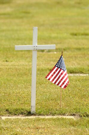 A small american flag sits next to a simple wood cross on Memorial Day  photo