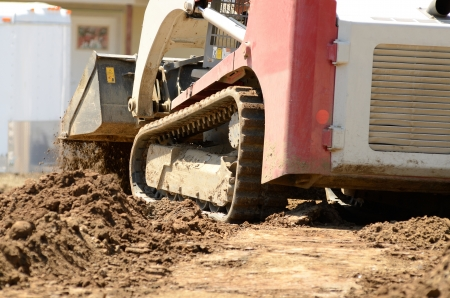Infrastructure excavation building contractors smoothing dirt over water lines in a utility trench at a commercial residential development