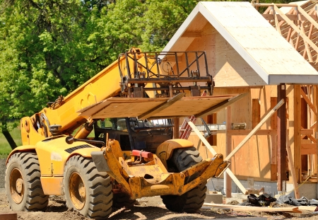 pivot: A roofing contractor moves plywood sheeting at a commercial residential development using a telehandler forklift truck Stock Photo