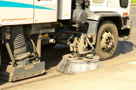 A street cleaner works to pick up grass at a two car accident resulting in minor injuries and one arrested for DUII