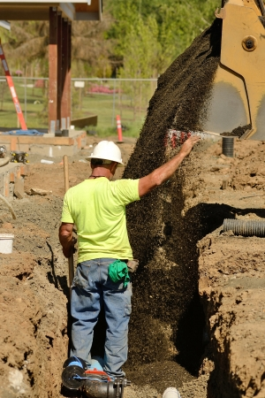 Infrastructure excavation building contractors installing water lines in a utility trench at a commercial residential development photo