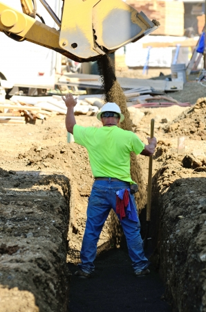 Infrastructure excavation building contractors installing water lines in a utility trench at a commercial residential development
