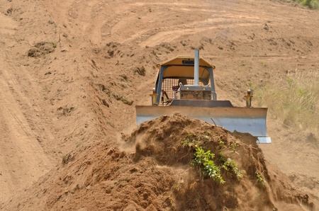 A small bulldozer works to remove top soil and duft with organic material from a new commercial development project