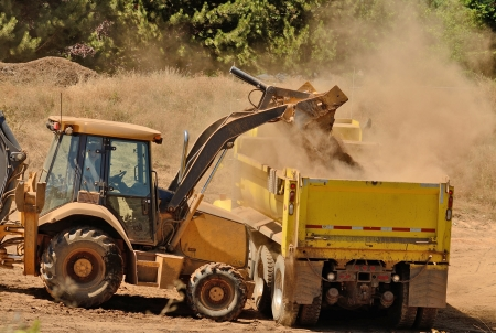 heavy industry: A backhoe loads duft and top soil into a 10-yard dump truck at a new commercial road development
