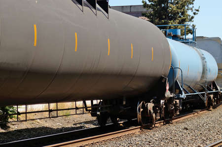 Train passes through an industrial section of a large northwest american city carrying hazardous materials in flammable liquid railroad tank cars