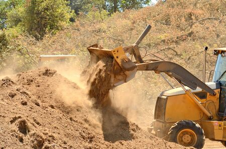 public works: Small backhoe moves dirt at a new commercial construction development project