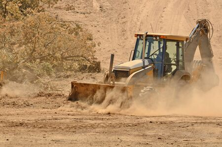 Small backhoe moves dirt at a new commercial construction development project photo