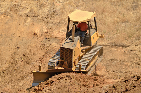 preperation: Small bulldozer clearing dirt from a hillside in preperation for a new commerical construction development