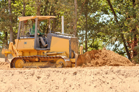 preperation: Small bulldozer moving dirt from a hillside in preperation for a new commerical construction development