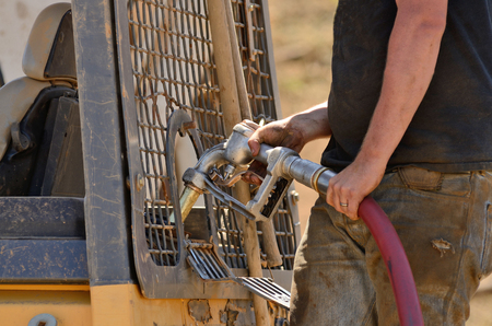 Equipment operator filling up the fuel tank of a small bulldozer with diesel fuel