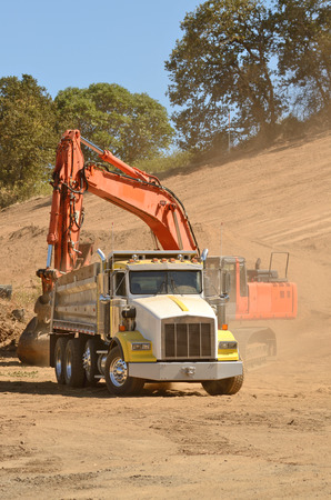 Track hoe excavator filling up a dump truck at  a new commerical construction development photo