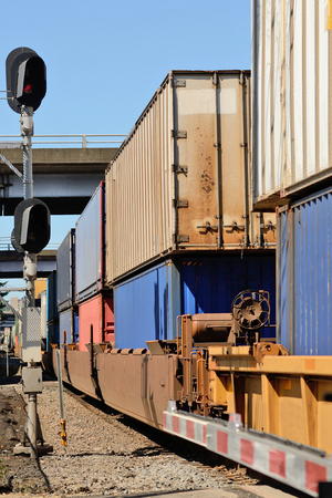 american city: Train passes through an industrial section of a large northwest american city with intermodal modular shipping containers