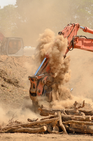 Track hoe excavator working on a top soil pile for later use on a new commercial construction development project photo