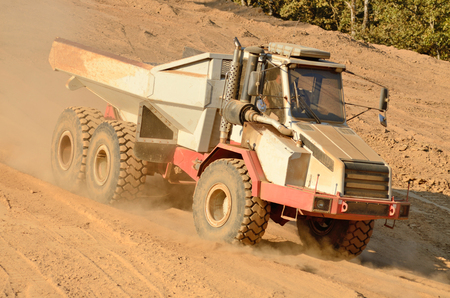 dump truck: A large articulated dump truck moves top soil pile for later use on a new commercial construction development project Stock Photo