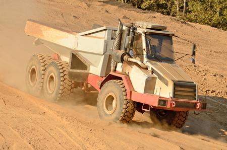 camion volteo: Un gran cami�n volquete articulado mueve pila capa superior del suelo para su posterior uso en un nuevo proyecto de desarrollo de la construcci�n comercial