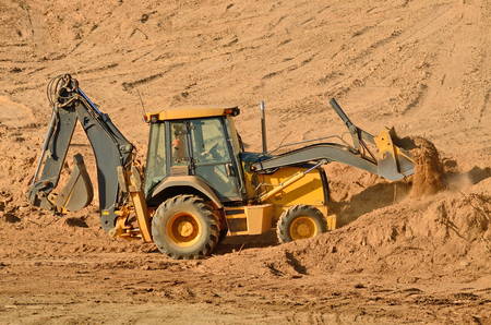 Backhoe excavator moving top soil for later use on a new commercial construction development project