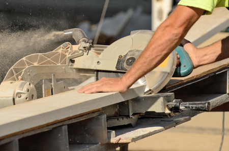 cut off saw: Carpenter uses a compound electric cut off saw to cut trim boards for a new commercial residential project