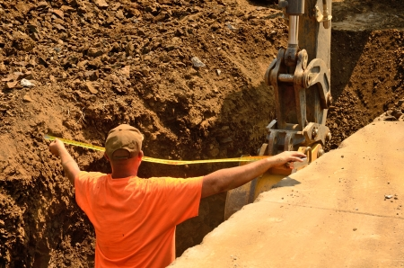A backhoe and crew dig a utility trench for gas and other electrical utilities at a new commercial construction development