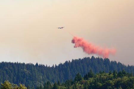retardant: Una nave cisterna aereo ritardante scende il suo carico rosso sopra le montagne dell'Oregon catena costiera del sud ai Douglas complesso forestale incendi vicino a Glendale