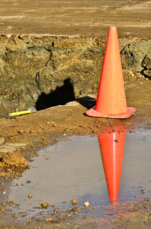 pot hole: traffic cone at the edge of a construciton trench