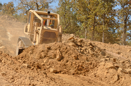 Large bulldozer moving rock and soil for fill for a new commercial development road construction project photo
