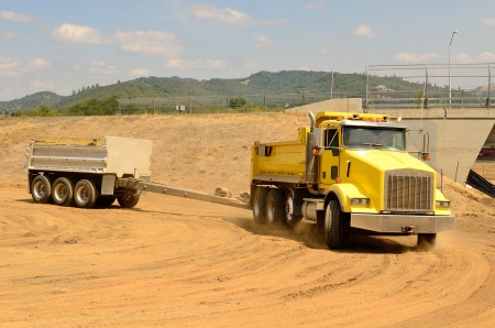 Tandum dump truck arrives at a new commercial construction development project for its load of dirt