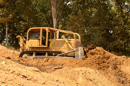pushes: Exchavator bulldozer pushes top soil and loose dirt down a hill at a new commercial construction development project