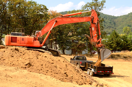 Exchavator track hoe loads a small dump trailer with top soil and loose dirt at a new commercial construction development project photo