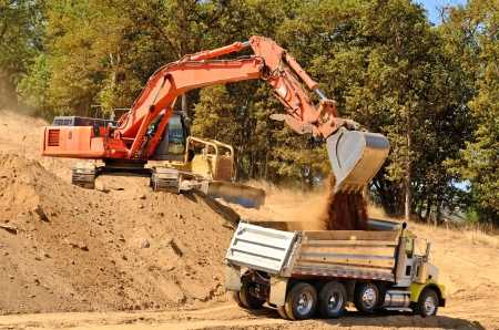 dump truck: Large track hoe excavator filling a dump truck with rock and soil for fill at a new commercial development road construction project