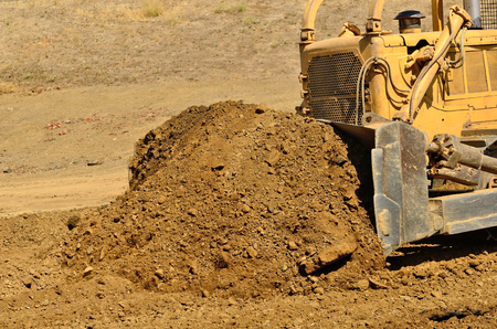 Large bulldozer moving rock and soil for a fill lift at a new commercial development road construction project photo