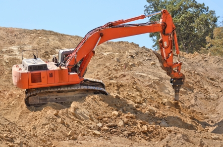 ripper: Large track hoe excavator using a claw ripper to break up rock and soil for fill for a new commercial development road construction project