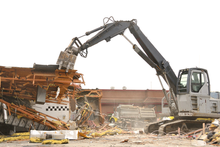 Large clamshell bucketed track hoe tearing down a former restuarant for a new commercial building project in Roseburg OR Stock Photo