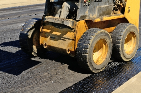 compact track loader: Small skid steer tractor moving asphalt on a repaving project Stock Photo