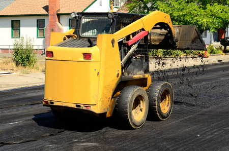 Small skid steer tractor moving asphalt on a repaving project photo