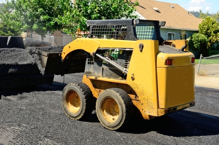 Small skid steer tractor moving asphalt on a repaving project Stock Photo