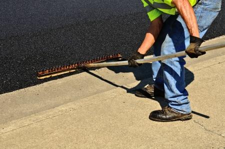 레이크를 사용하는 작업자는 repaving의 constuction 프로젝트에 콘크리트 연석 스톤 떨어져 초과 아스팔트를 밀어