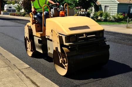 A small roller or compactor works on a layer of asphalt during  a repaving construciton project
