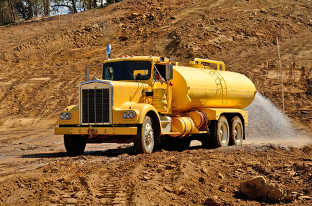 compacting: A water truck sprays water on a fresh fill layer of soil and rock for a new road construciton project