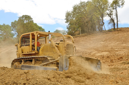 A large bulldozer spreads dirt and rock for a new fill layer on a commercial construciton road project photo