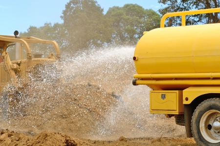 A water truck sprays water on a fresh fill layer as a large bulldozer spreads soil and rock for a new road construciton project.