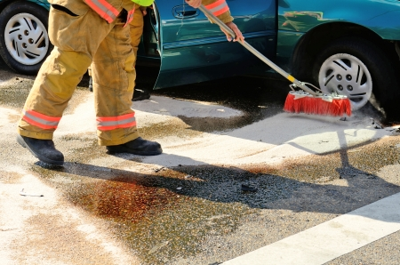 Fire fighters clean up spilt fluids at a two vehicle head on accident at an intersection in Roseburg, OR on August 27, 2013