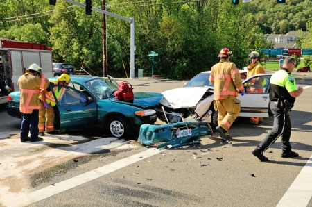 emt: Fire fighters and paramedic emt personnel extricate the victim of a two vehicle head on accident at an intersection in Roseburg, OR on August 27, 2013