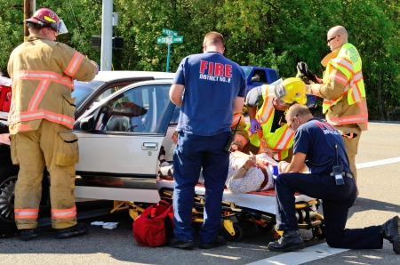 Fire fighters and paramedic emt personnel extricate the victim of a two vehicle head on accident at an intersection in Roseburg, OR on August 27, 2013